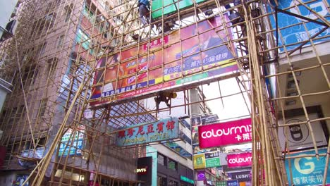 Pan-up-from-a-busy-commercial-district-in-Hong-Kong-China-to-reveal-workers-on-bamboo-scaffolding-2