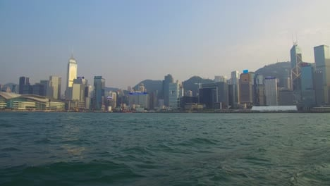 Establishing-shot-from-the-ferry-boat-reveals-Hong-Kong-harbor-and-skyline-with-clouds-1
