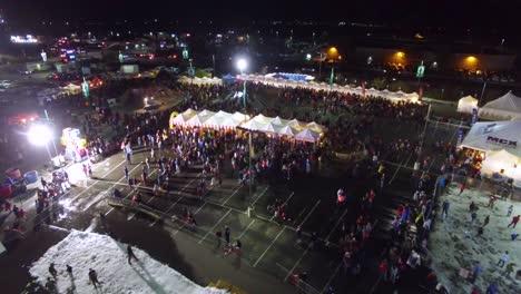 Antena-Sobre-Un-Carnaval-O-Feria-Celebrada-En-El-Estacionamiento-De-Un-Centro-Comercial-Con-Multitudes-Y-Puestos-Y-Atracciones