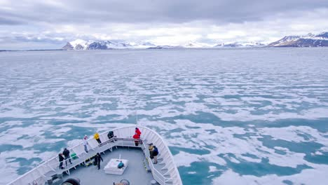 A-POV-time-lapse-shot-of-a-ship-bow-icebergs-and-tourists-passing-through-Bellsund-Bay-or-fjord-in-Norway