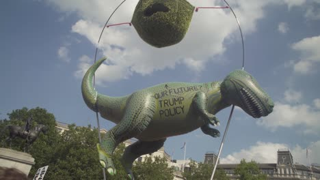 A-Huge-Green-Dinosaur-Doll-Above-Huge-Crowds-Of-Protesters-Gathering-On-The-Streets-Of-London-To-Protest-The-Visit-Of-US-President-Donald-Trump