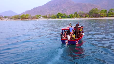 Aerial-over-a-small-dive-tour-boat-filled-with-tourists-off-the-coast-of-Monkey-Bay-Malawi