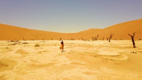 Antena-Siguiendo-A-Una-Mujer-Corriendo-Cerca-De-árboles-Muertos-En-Sossusvlei-Desierto-Dunas-De-Arena-En-El-Desierto-De-Namib-Namibia-África
