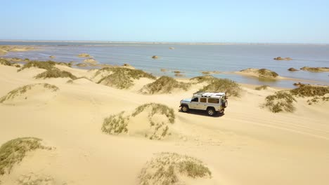 Aerial-over-a-4WD-safari-jeep-vehicle-driving-across-the-sand-dunes-and-Skeleton-Coast-of-Namibia-Africa