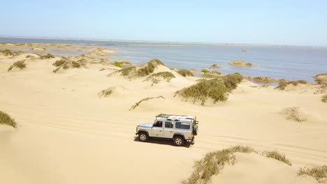 Vista-Aérea-over-a-4WD-safari-jeep-vehicle-conduciendo-across-the-sand-dunes-and-Skeleton-Coast-of-Namibia-Africa-1
