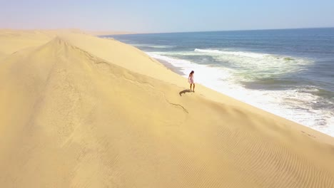 Aerial-over-a-model-released-woman-walking-on-magnificent-sand-dunes-on-the-Skeleton-Coast-Namibia