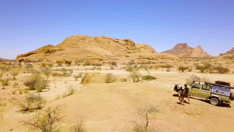 Antena-Sobre-Una-Pareja-Caminando-Cerca-De-Un-Jeep-Safari-4wd-En-El-Accidentado-Paisaje-Desértico-De-Spitzkoppe-Namibia-África