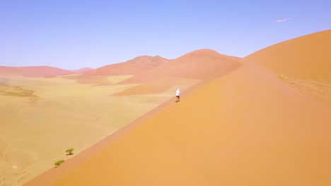 Aerial-over-a-man-hiking-in-the-rugged-desert-landscape-and-sand-dunes-near-Dune-45-in-Namibia-Africa-2