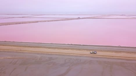 Aerial-over-a-4WD-safari-vehicle-driving-on-a-colorful-pink-salt-flat-region-in-Namibia-Africa