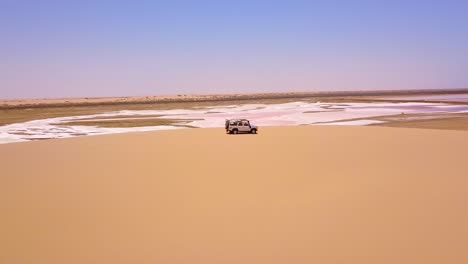 Vista-Aérea-over-a-4WD-safari-vehicle-conduciendo-on-a-colorful-pink-salt-flat-region-in-Namibia-Africa-1