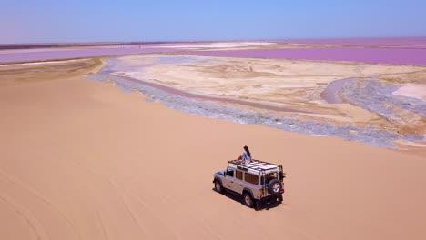 Increíble-Antena-Sobre-Una-Mujer-Sentada-En-La-Parte-Superior-De-Un-Jeep-Safari-4wd-En-Una-Colorida-Región-Rosada-Del-Salar-En-Namibia-África