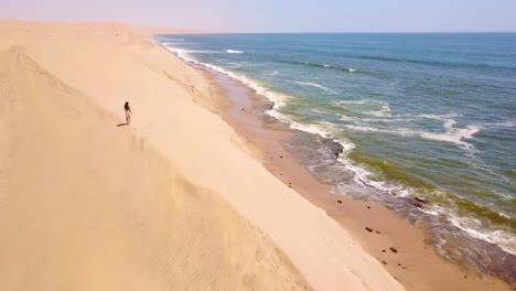 Aerial-over-a-model-released-woman-walking-on-magnificent-sand-dunes-on-the-Skeleton-Coast-Namibia-1