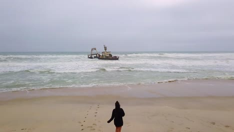 Amazing-aerial-over-a-woman-jogging-or-running-towards-a-shipwreck-along-the-Skeleton-Coast-of-Namibia-Africa-1