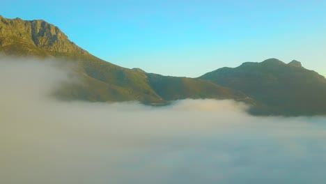 Drone-aerial-above-the-clouds-looking-at-Table-Mountain-and-Twelve-Apostles-behind-Cape-Town-South-Africa