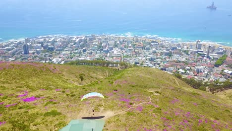 Drone-aerial-over-paragliding-and-paragliders-with-the-downtown-city-of-Cape-Town-South-Africa-in-background-2