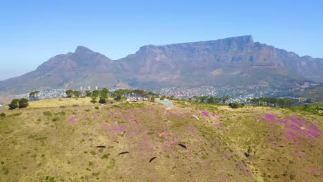 Drone-aerial-over-paragliding-and-paragliders-with-Table-Mountain-Cape-Town-South-Africa-in-background