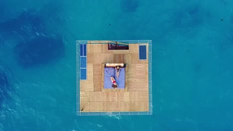 Aerial-drone-shot-over-the-Manta-Resort-underwater-hotel-in-Tanzania-Africa-with-a-man-and-woman-lounging-on-the-platform-over-the-ocean