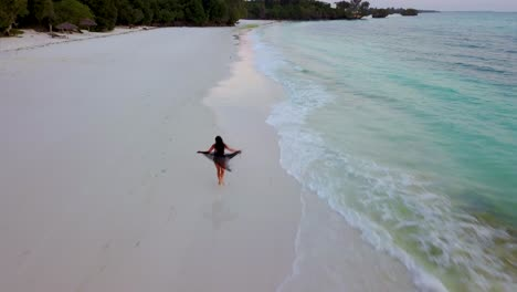 Aerial-drone-shot-of-a-woman-model-running-freely-along-a-white-sand-tropical-beach-in-a-flowing-dress-or-skirt