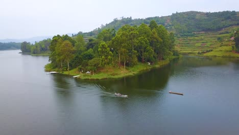Aerial-over-a-motorboat-longboat-canoe-traveling-on-a-lake-in-a-lush-part-of-Uganda-Africa-1