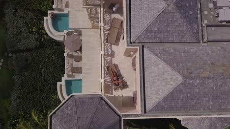 Aerial-rise-up-view-of-a-woman-model-relaxing-on-a-porch-or-deck-of-a-luxury-resort-hotel-or-condo-in-Barbados-Caribbean