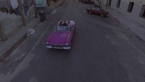 Rising-drone-aerial-of-a-group-of-tourists-riding-in-a-classic-old-car-through-the-streets-of-Havana-Cuba