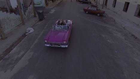 Aufsteigende-Drohnenantenne-Einer-Gruppe-Von-Touristen-Die-In-Einem-Alten-Oldtimer-Durch-Die-Straßen-Von-Havanna-Kuba-Fahren