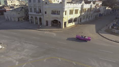 Drone-aerial-of-a-group-of-tourists-riding-in-a-classic-old-car-through-the-streets-of-Havana-Cuba