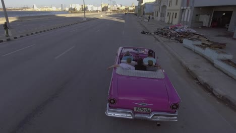 Drone-aerial-of-a-group-of-tourists-riding-in-a-classic-old-car-through-the-streets-of-Havana-Cuba-1
