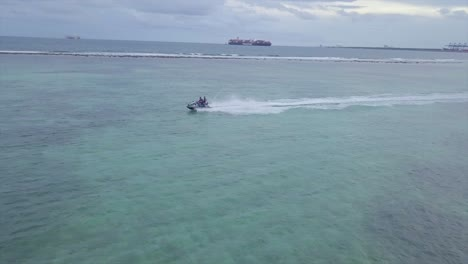 Aerial-of-two-men-riding-a-jet-ski-in-the-Boca-Chica-beach-region-of-the-Dominican-Republic