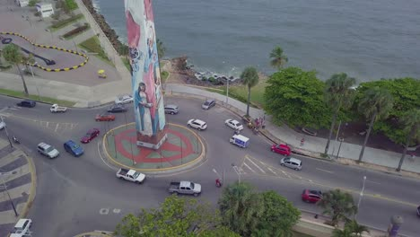 Aerial-over-a-painted-Christian-statue-at-a-traffic-circle-roundabout-in-Santo-Domingo-the-capital-of-the-Dominican-Republic