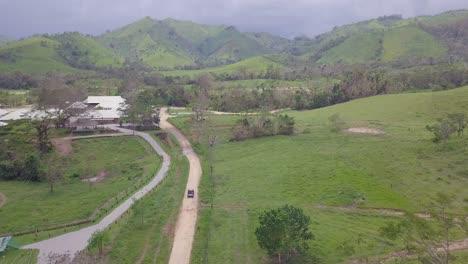 Vista-Aérea-of-a-vehicle-conduciendo-through-the-barren-green-landscapes-of-the-Dominican-Republic