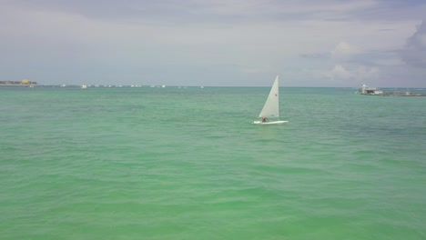 Aerial-over-tourist-sailing-a-small-sailboat-in-the-Boca-Chica-beach-district-in-the-Dominican-Republic
