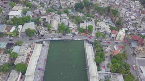 Vista-Aérea-over-the-slums-favela-and-shanty-towns-in-the-Cite-Soleil-district-of-Port-Au-Prince-Haiti-with-soccer-stadium-foreground