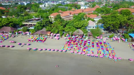 Aerial-over-colorful-beach-umbrellas-in-Sanur-or-Kuta-beach-on-the-coast-of-Bali-Indonesia