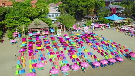Aerial-over-colorful-beach-umbrellas-in-Sanur-or-Kuta-beach-on-the-coast-of-Bali-Indonesia-2