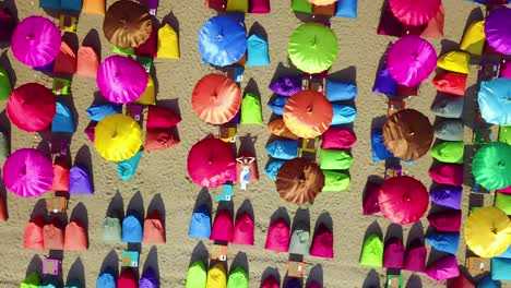 Aerial-over-a-woman-relaxing-beneath-colorful-beach-umbrellas-in-Sanur-or-Kuta-beach-on-the-coast-of-Bali-Indonesia