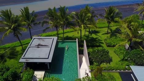 Antenne-über-Einer-Frau-Die-In-Einem-Infinity-Pool-Im-Luxusresort-Eines-Eleganten-Wohnkomplexes-Entlang-Der-Küste-Von-Bali-Indonesien-Schwimmt-