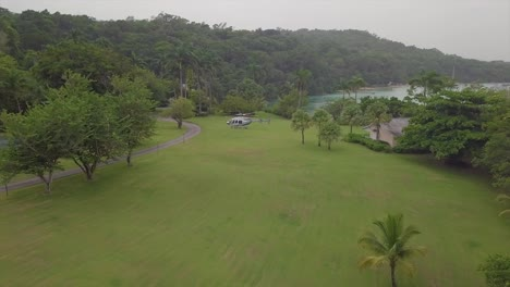 Move-in-aerial-of-a-Sandal-s-resort-helicopter-sitting-on-a-grassy-open-space-on-a-luxurious-tropical-island-in-Jamaica