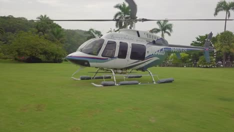 Move-around-vista-aérea-of-a-Sandal\-s-resort-helicopter-sitting-on-a-grassy-open-space-on-a-luxurious-tropical-island-in-Jamaica