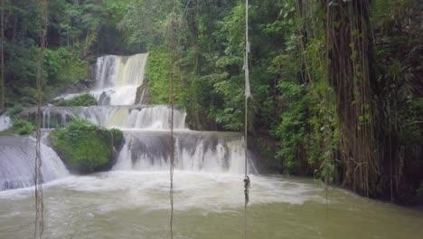 Aerial-reveals-man-swinging-by-rope-into-YS-falls-in-Saint-Elizabeth-parish-Jamaica