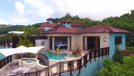 Aerial-of-a-sexy-woman-walking-out-to-a-pool-of-a-condo-or-luxury-home-on-the-Caribbean-Island-of-St-Lucia
