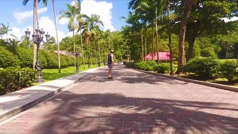 A-man-rides-a-skateboard-down-a-brick-driveway-on-a-tropical-caribbean-island