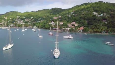 Hermosa-Antena-De-Un-Velero-Navegando-Por-El-Mar-Caribe-Cerca-De-La-Isla-De-San-Vicente-Con-Arco-Iris-Y-Costa-Distante