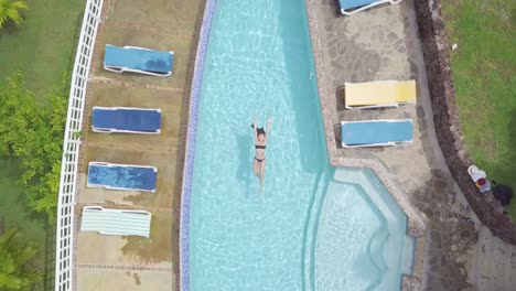 Aerial-of-a-sexy-woman-relaxing-at-a-pool-of-a-condo-or-luxury-home-on-the-Caribbean-Island-of-St-Lucia