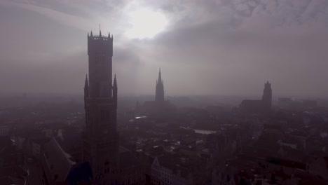 Vista-Aérea-of-a-mysterious-foggy-day-of-Bruges-Belgium-with-cathedral-churches-and-spires-in-distance