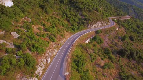 Vista-Aérea-over-three-people-riding-mopeds-or-Vespa-scooters-along-a-two-land-montaña-road-in-Croatia