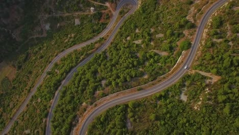 Vista-Aérea-of-cars-navigating-on-a-very-narrow-winding-montaña-road-with-many-switchbacks-and-hairpin-turns
