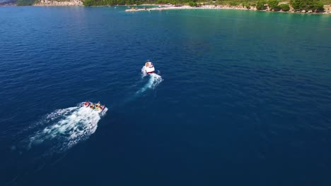 Aerial-of-adventure-boat-towing-four-innertubes-for-a-tubing-adventure-off-the-coast-of-Croatia