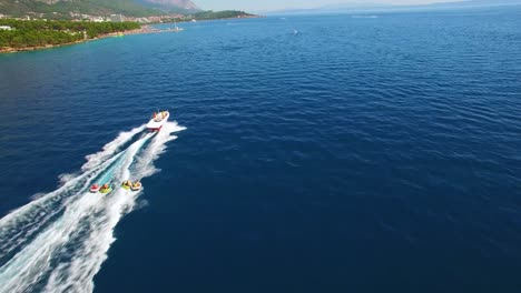 Aerial-of-adventure-boat-towing-four-innertubes-for-a-tubing-adventure-off-the-coast-of-Croatia-1