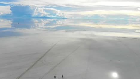 Aerial-of-people-gathering-on-the-Uyuni-salt-flats-lake-with-perfect-reflections-in-Bolivia